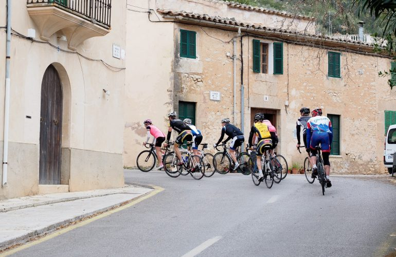 Cycling club group riding through Pyrenees village